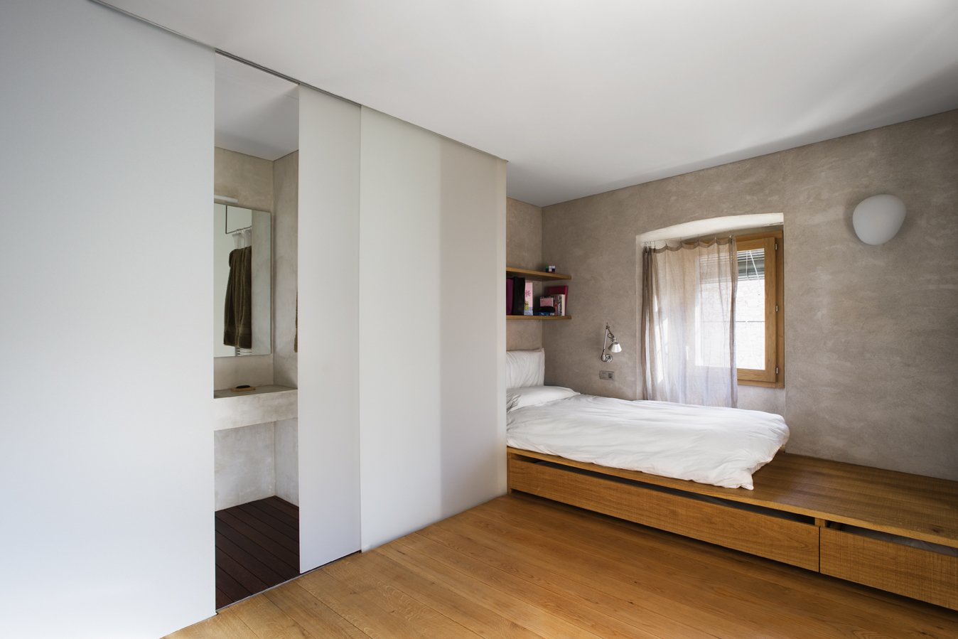 Bedroom, Wall Lighting, Storage, Medium Hardwood Floor, Shelves, and Bed A warm and simple bedroom with an ensuite bathroom.  Photo 6 of 15 in A Spanish Architect Transforms a Medieval Townhouse Into a Stunning Rental