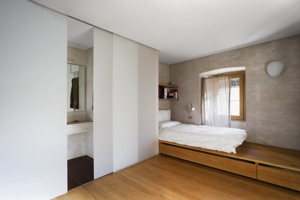 Bedroom, Wall, Storage, Medium Hardwood, Shelves, and Bed A warm and simple bedroom with an ensuite bathroom.  Best Bedroom Medium Hardwood Storage Photos from A Spanish Architect Transforms a Medieval Townhouse Into a Stunning Rental