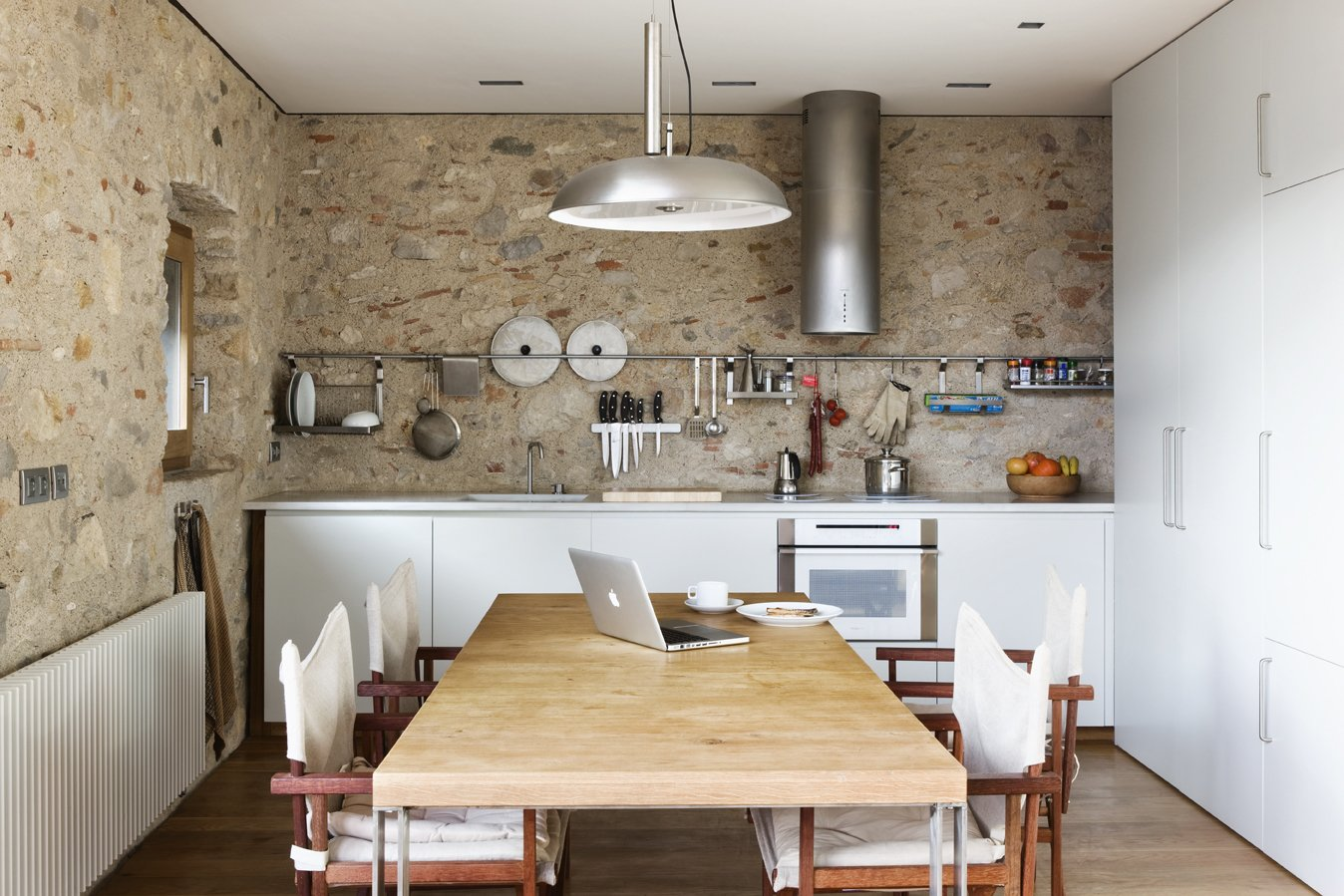 Kitchen, Stone Slab, Laminate, White, Medium Hardwood, Range Hood, Drop In, Wall Oven, Cooktops, Pendant, and Recessed The original 16th century stone walls are left exposed in the kitchen.  Best Kitchen Medium Hardwood Laminate Photos from A Spanish Architect Transforms a Medieval Townhouse Into a Stunning Rental