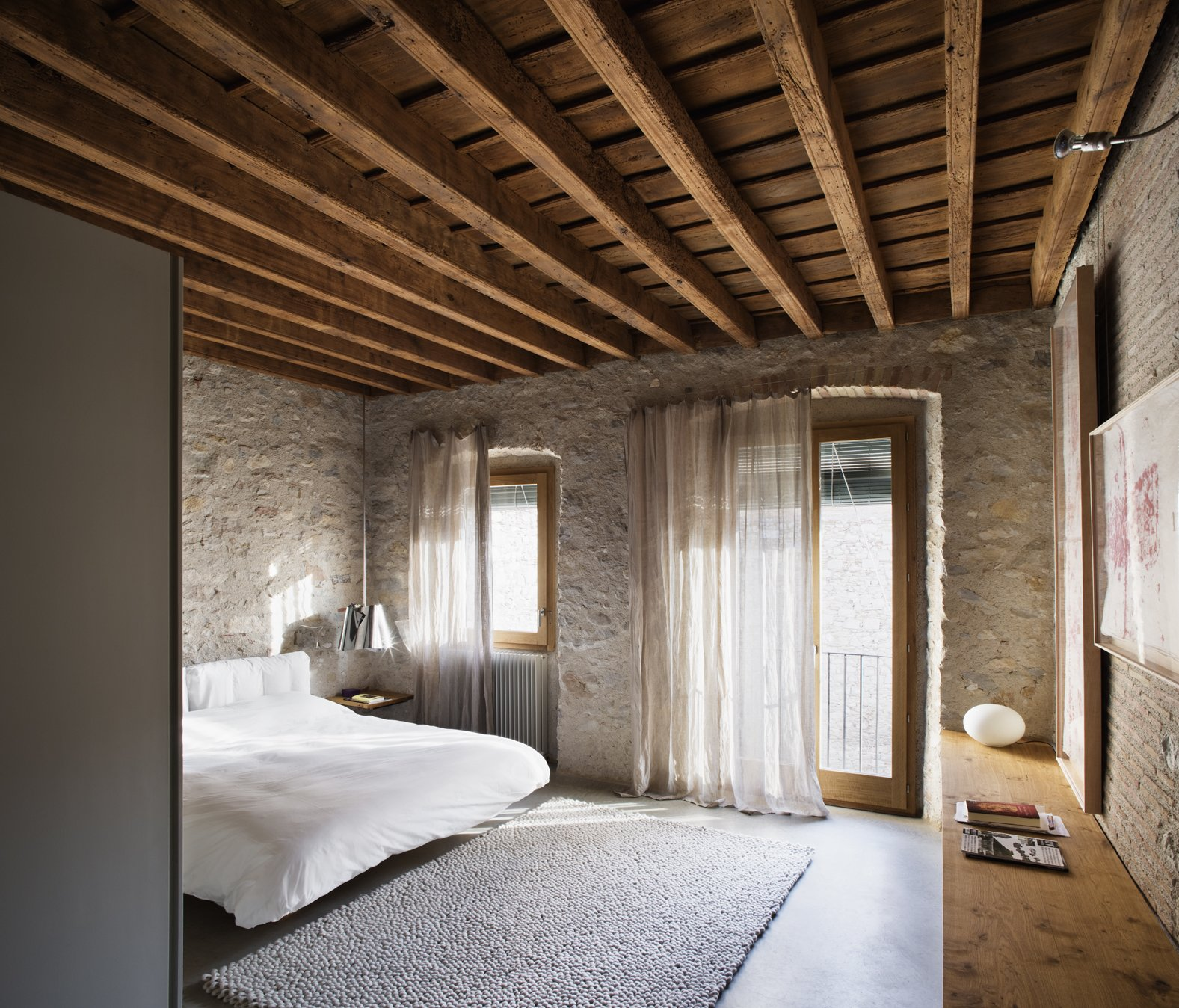Bedroom, Table Lighting, Night Stands, Concrete Floor, Lamps, Bed, Rug Floor, and Wall Lighting A dialogue between ancient and contemporary can be seen in the bedroom.  Photo 10 of 15 in A Spanish Architect Transforms a Medieval Townhouse Into a Stunning Rental