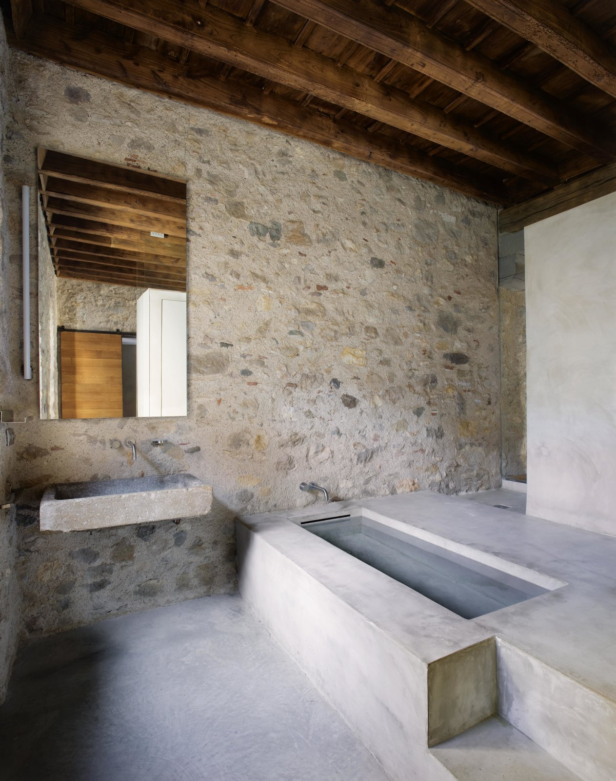 Bath Room, Wall Mount Sink, Concrete Floor, Stone Slab Wall, and Drop In Tub A clean-lined bathroom of stone and concrete.  Photo 11 of 15 in A Spanish Architect Transforms a Medieval Townhouse Into a Stunning Rental
