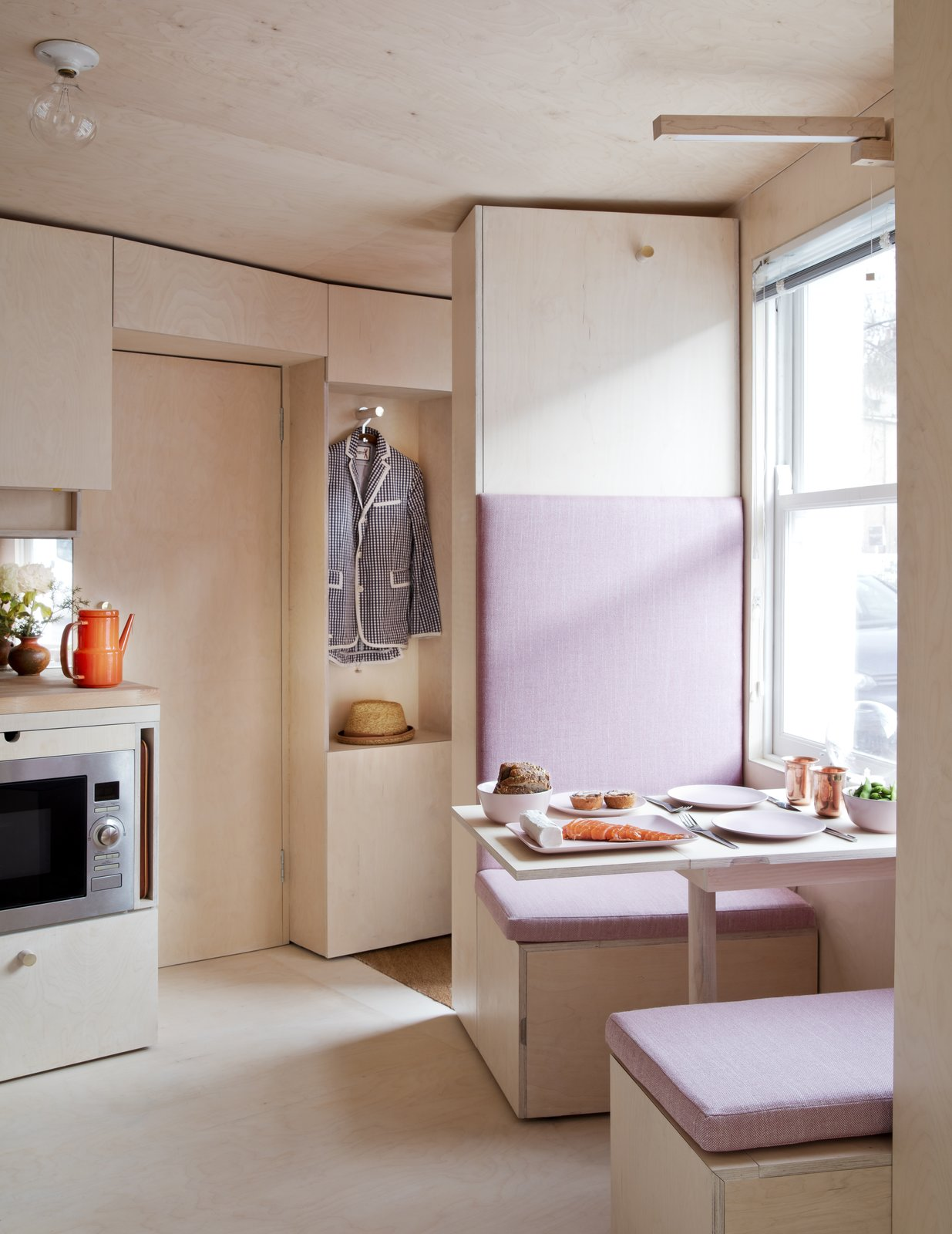 Dining Room, Table, Ceiling Lighting, Light Hardwood Floor, and Bench A breakfast booth that looks out to the street.  Photo 13 of 21 in 10 Things You Should Know Before Moving Into a Tiny Home from This Tiny 140-Square-Foot Apartment Boasts Comfort and Function