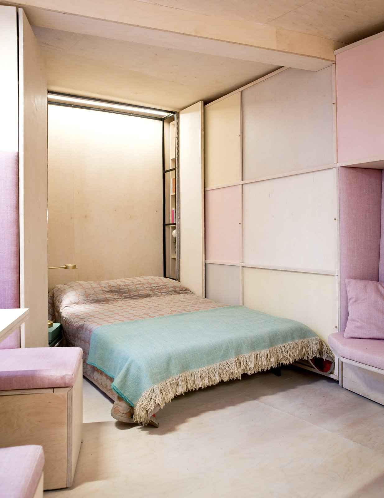 A Murphy bed located along the narrowest wall of the triangular-shaped apartment. Tagged: Bedroom, Bed, Light Hardwood, Night Stands, Storage, Lamps, and Table.  Best Bedroom Bed Lamps Photos from This Tiny 140-Square-Foot Apartment Boasts Comfort and Function