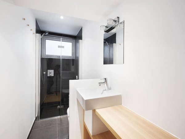 The bathroom has an elevated shower area with frosted glass windows that look out to a quiet alley.