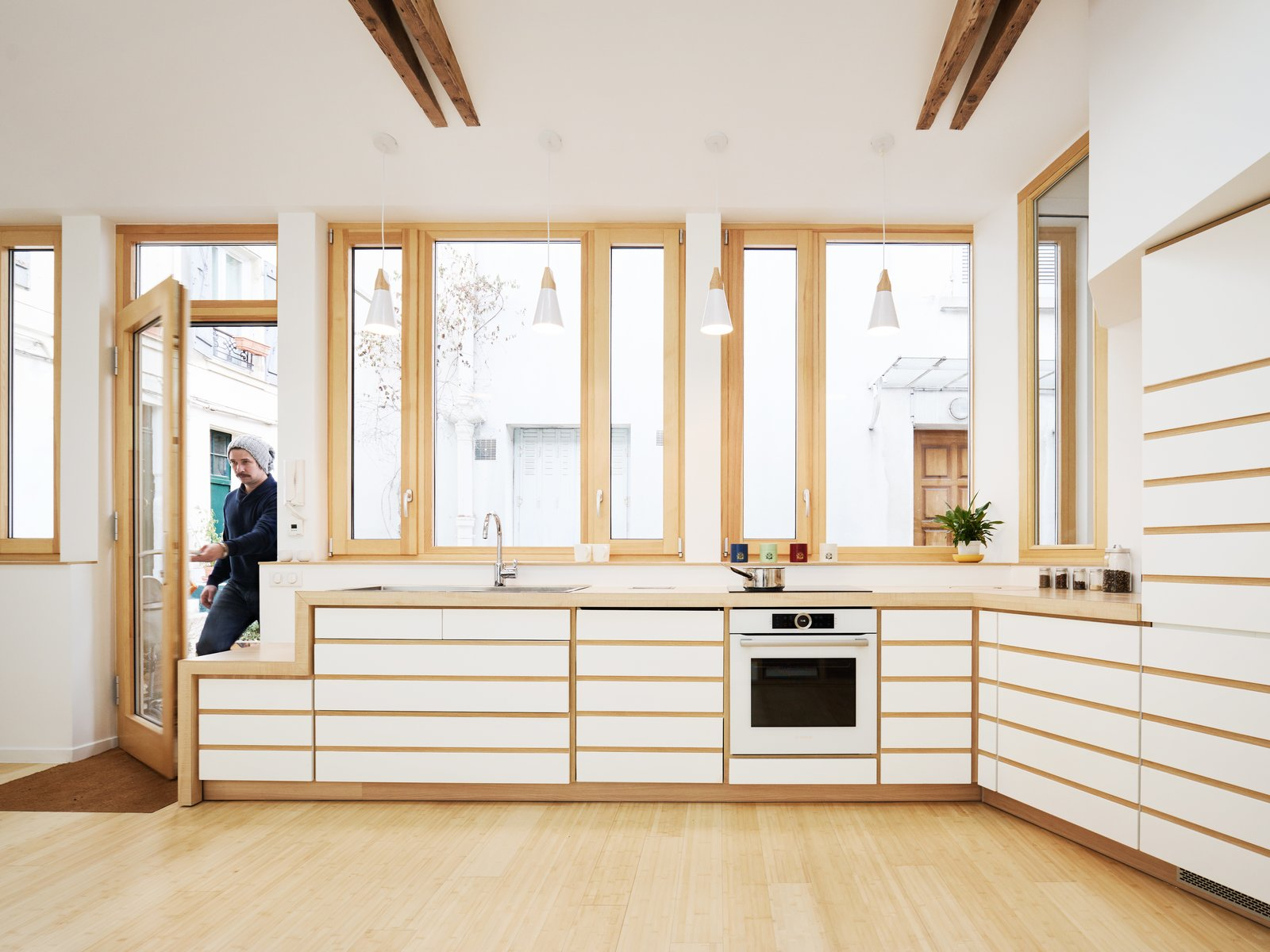 Kitchen, Drop In, Wall Oven, Light Hardwood, White, Wood, Pendant, Wood, and Cooktops The white cabinetry with beech wood details adds a little Zen to the kitchen.  Best Kitchen Wood Wood Drop In Pendant Photos from Before & After: A Renovated Artist's Studio Is Now an Airy, Efficient Home