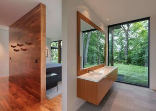The bathroom has a large window that frames tree views.