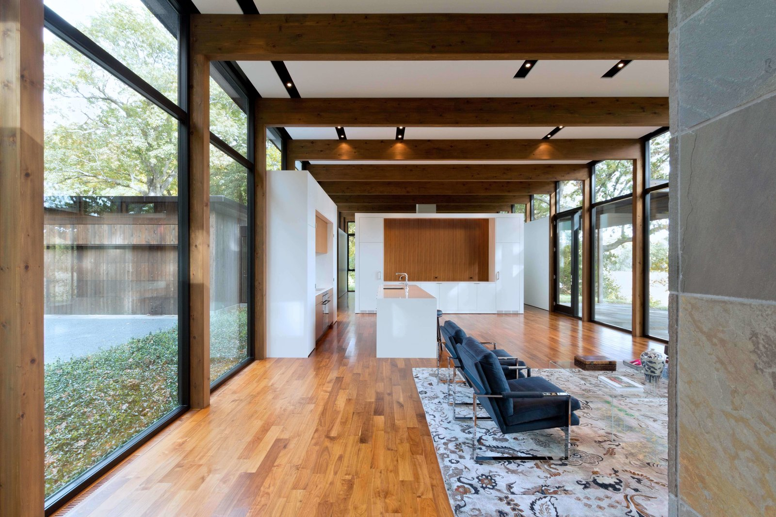 "Living, Medium Hardwood, Rug, Recessed, Chair, and Coffee Tables The glossy white kitchen gives the open-plan living space a clean and modern look.  Best Kitchen Track Wood Photos from This Glass House and ""Shiny Shed"" Merge With Nature in Minnesota"