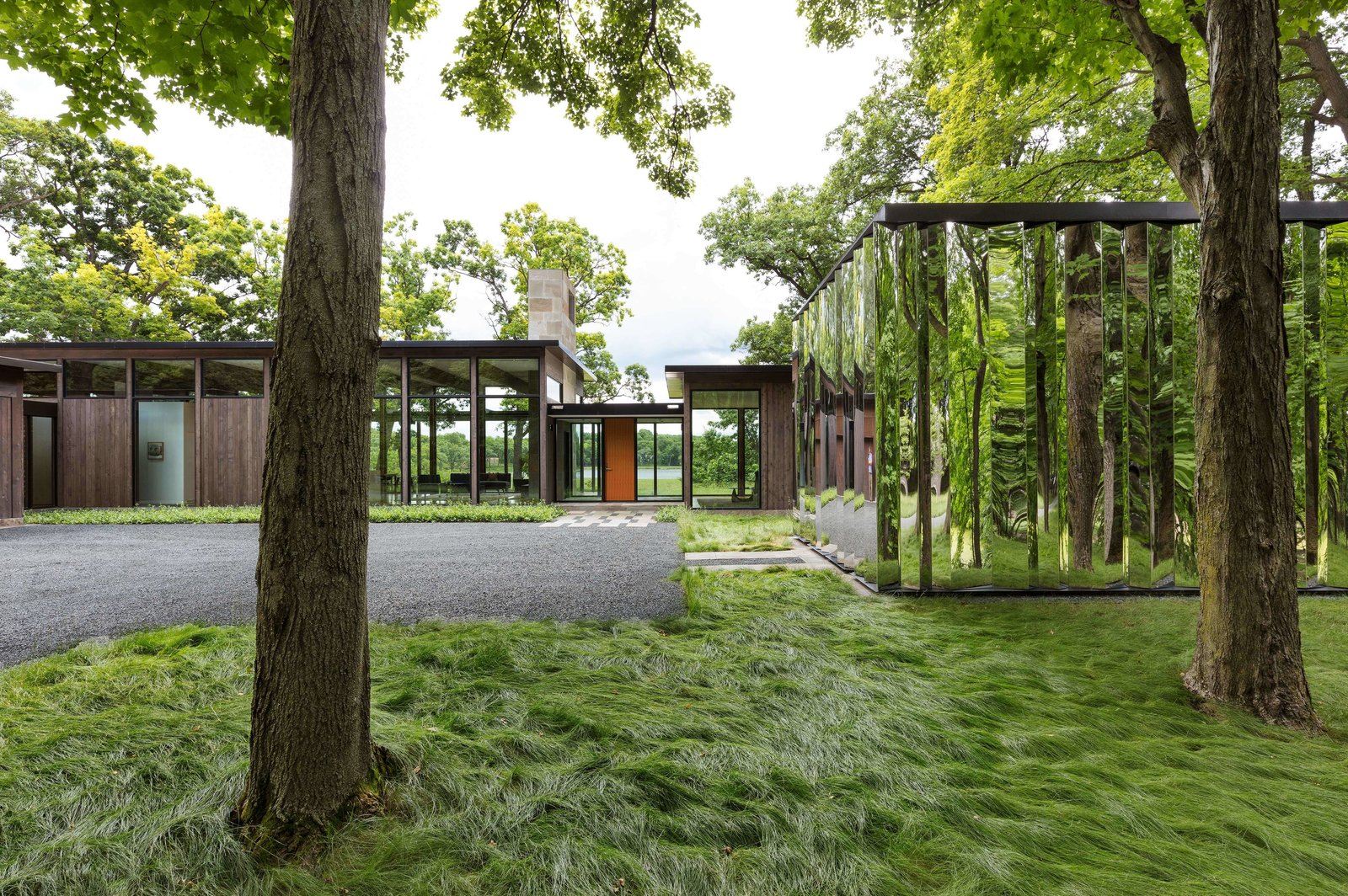"Exterior, Flat RoofLine, Metal Roof Material, Wood Siding Material, Glass Siding Material, Metal Siding Material, and House Building Type Minneapolis–based firm ALTUS Architecture + Design have designed a unique 2,850-square-foot residence in Woodland, Minnesota, by marrying glass-house architecture with a reflective ""shiny"" shed. The single-story property is primed for tranquility, as it sits on a peaceful woodland plateau and overlooks a lush wetland, as well as a calming lake in the distance.  Best Photos from 50 Jaw-Dropping Glass Houses That Shatter Expectations"