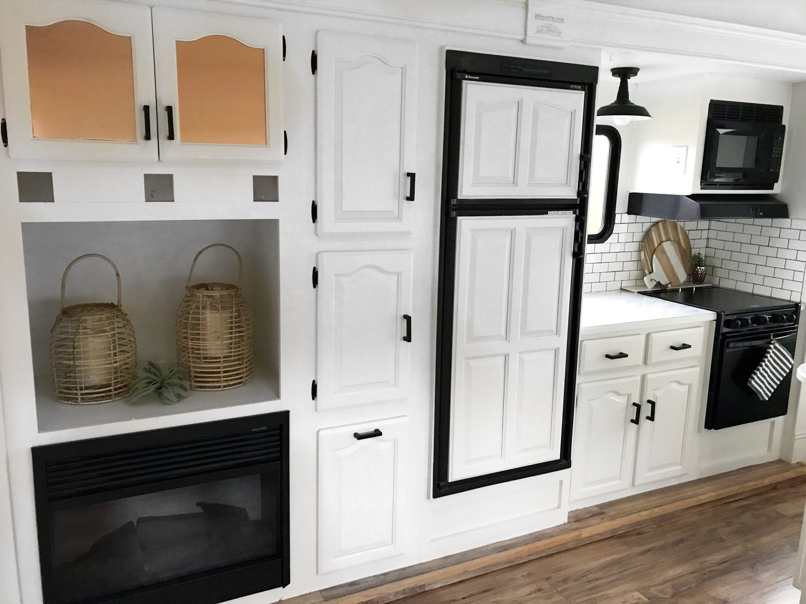 Kitchen, Medium Hardwood Floor, Cooktops, Subway Tile Backsplashe, Microwave, Wall Oven, and White Cabinet The kitchen has a fireplace, oven, microwave, electric cooktop and plenty of discreet storage.  Photo 10 of 16 in Hit the Road With This Chic Camper on Sale For $28K