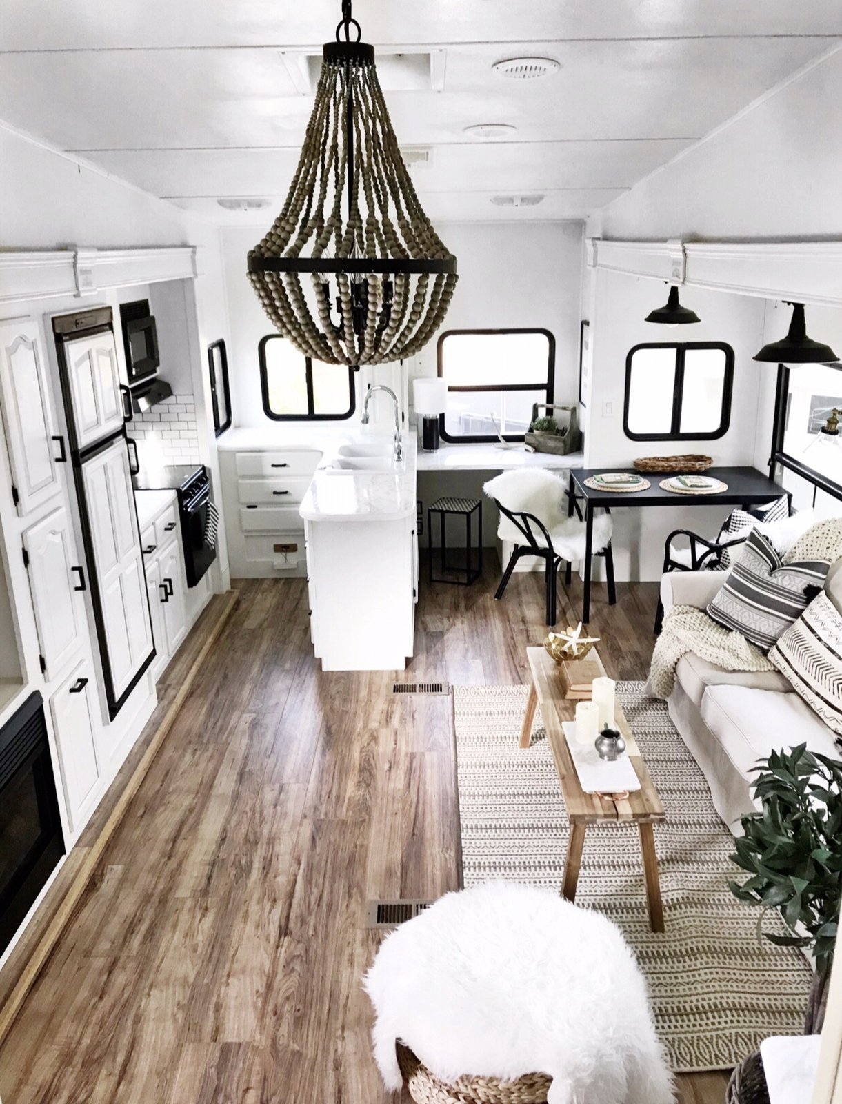Living Room, Sofa, Medium Hardwood Floor, Table, Pendant Lighting, Storage, Coffee Tables, and Rug Floor Wood details and a simple white and black color scheme give the RV's interior a bright, modern Scandinavian feel.  Photo 1 of 16 in Hit the Road With This Chic Camper on Sale For $28K