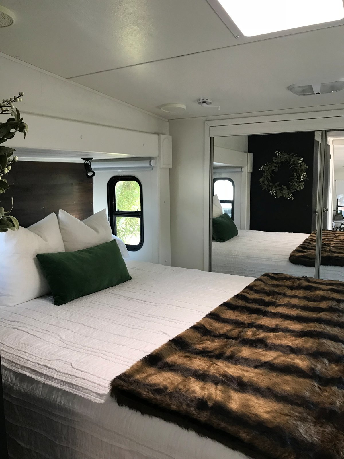 Bedroom, Bed, Wardrobe, and Ceiling Lighting A skylight window illuminates the bedroom, which appears larger than it is because of the closet with mirror-clad sliding doors.  Photo 6 of 16 in Hit the Road With This Chic Camper on Sale For $28K