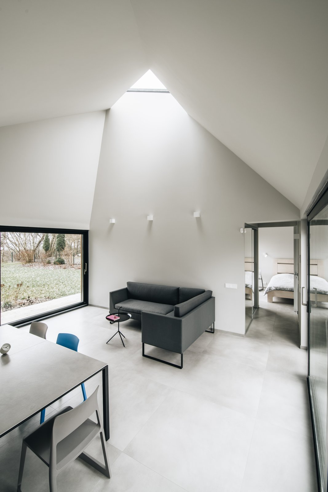 Living Room, Sofa, Wall Lighting, End Tables, Table, and Chair Fully-glazed walls on two sides, and a triangular skylight flood the living areas with light.  Photo 10 of 13 in This Forest Retreat Is a Modern Take on the Traditional Estonian Hut