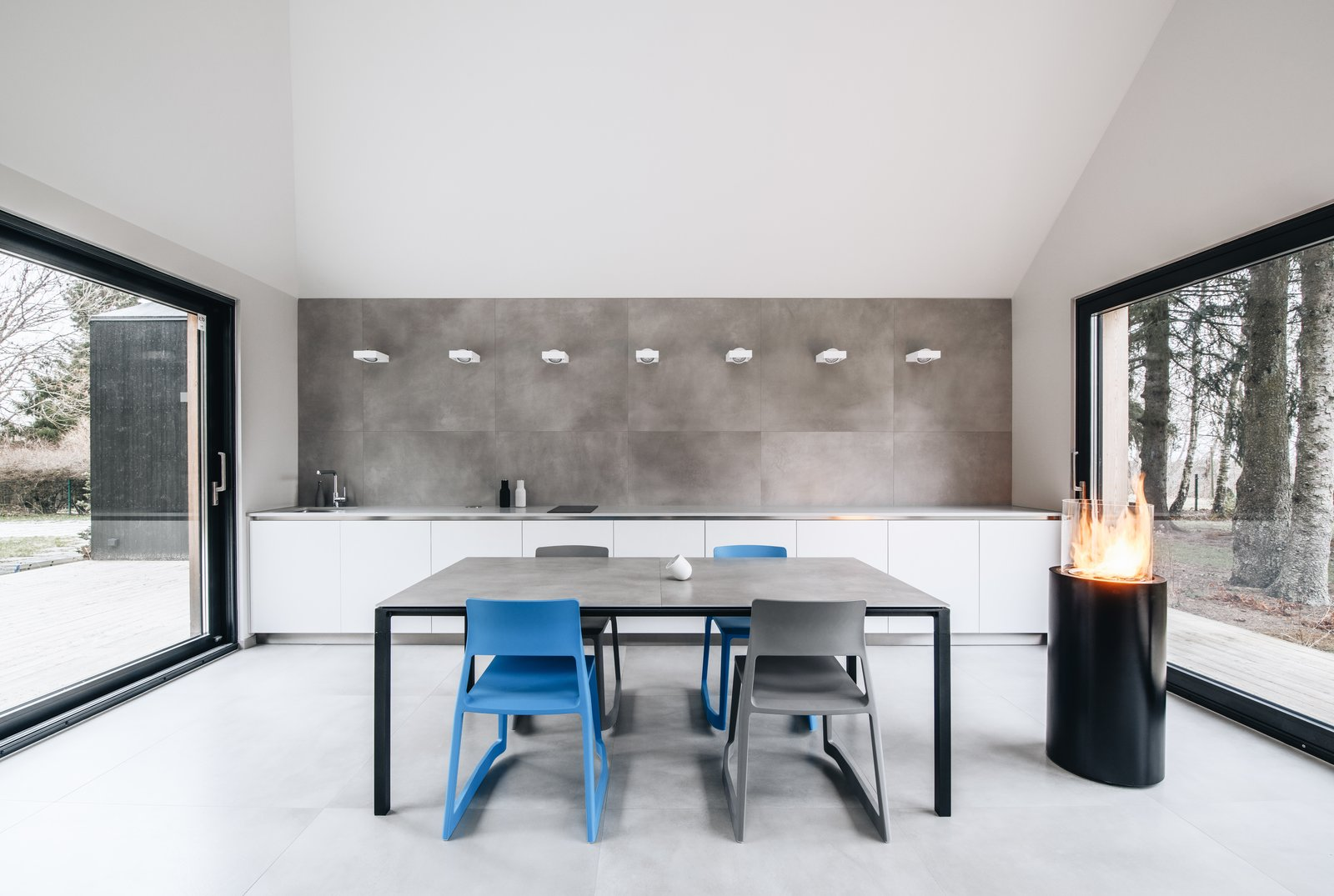 Dining Room, Table, Chair, and Wall Lighting The simple, fuss-free kitchen and dining area flows into the living lounge.  Photo 7 of 13 in This Forest Retreat Is a Modern Take on the Traditional Estonian Hut