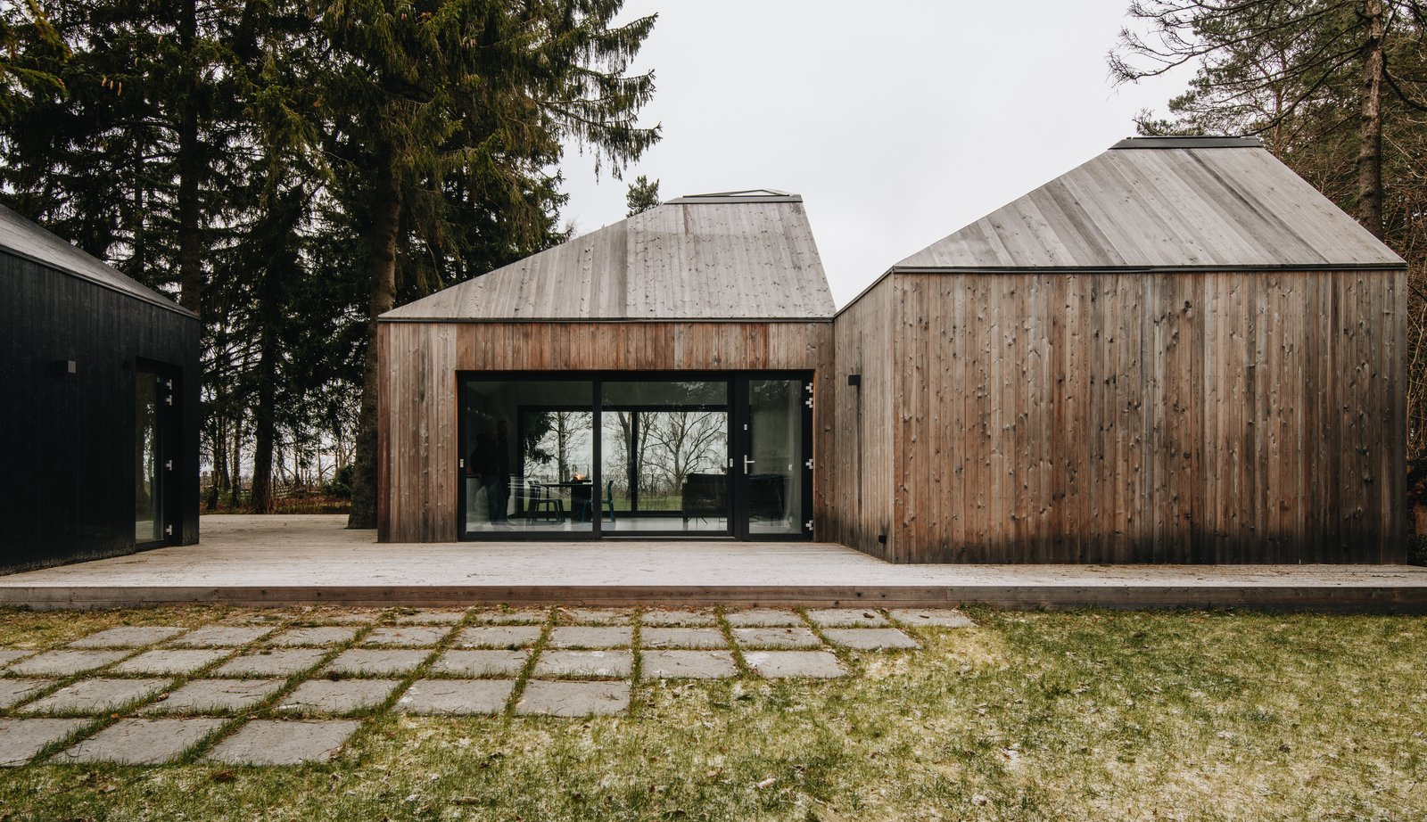 Exterior, Cabin Building Type, Wood Siding Material, and House Building Type The living areas have north and south facing glass walls.  Photo 5 of 13 in This Forest Retreat Is a Modern Take on the Traditional Estonian Hut