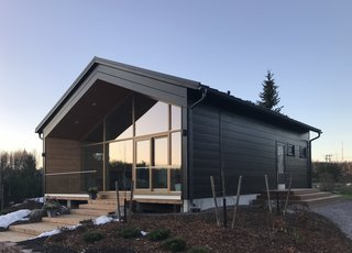 Designed by architect Tanja Rytkönen, Vista is a compact log home with a high pitched roof, and fully glazed façade.