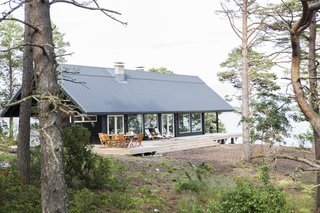 Designed by architects and experienced sailor Kari Leppänen, Honka's Saari villa was built with 134-milimeter thick square logs treated with a dark finish, and has three-meter wide eaves that provide shade, and wind protection for the outdoor patio.
