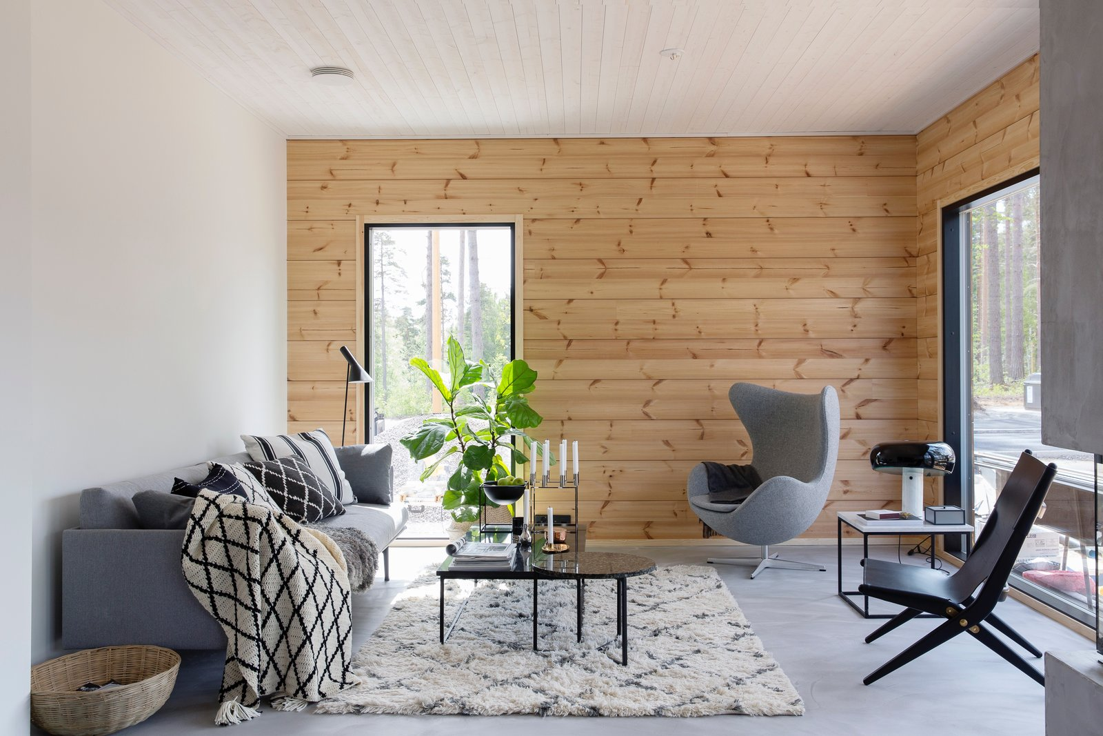 Living Room, Coffee Tables, Sofa, Chair, Floor Lighting, Rug Floor, and Table Lighting The living room of Ink, a Honka Fusion home furnished by interior designer Jonna Kivilahti.  Best Photos from These 8 Log Cabin Kit Homes Celebrate Nordic Minimalism