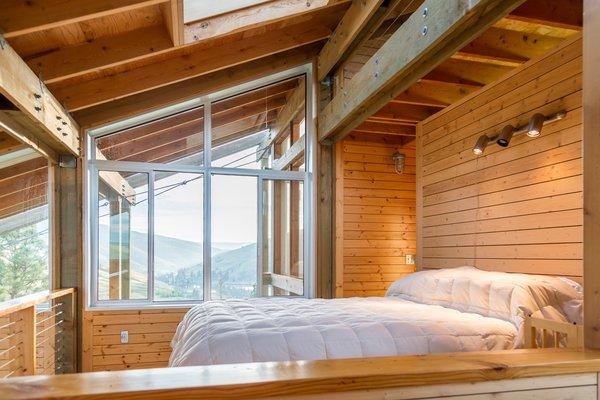 The lofted bedroom has a snug, cabin-like feel.