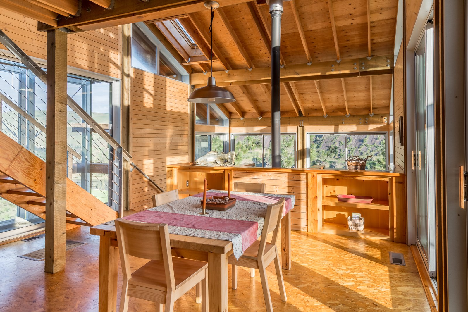 Dining, Shelves, Table, Chair, Pendant, and Plywood A staircase leads up from the dining and kitchen area to a mezzanine loft bedroom.  Best Dining Shelves Table Plywood Photos from Own This Award-Winning Riverside Home in Idaho For $650K