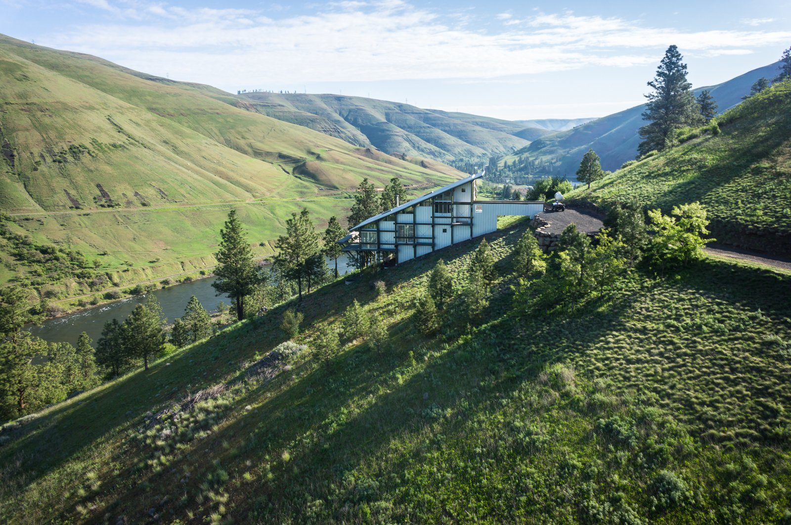 The western side of the house has a scaffold-like structure for window cleaning. Tagged: Outdoor, Trees, Slope, Woodland, and Grass.  Best Outdoor Slope Trees Photos from Own This Award-Winning Riverside Home in Idaho For $650K