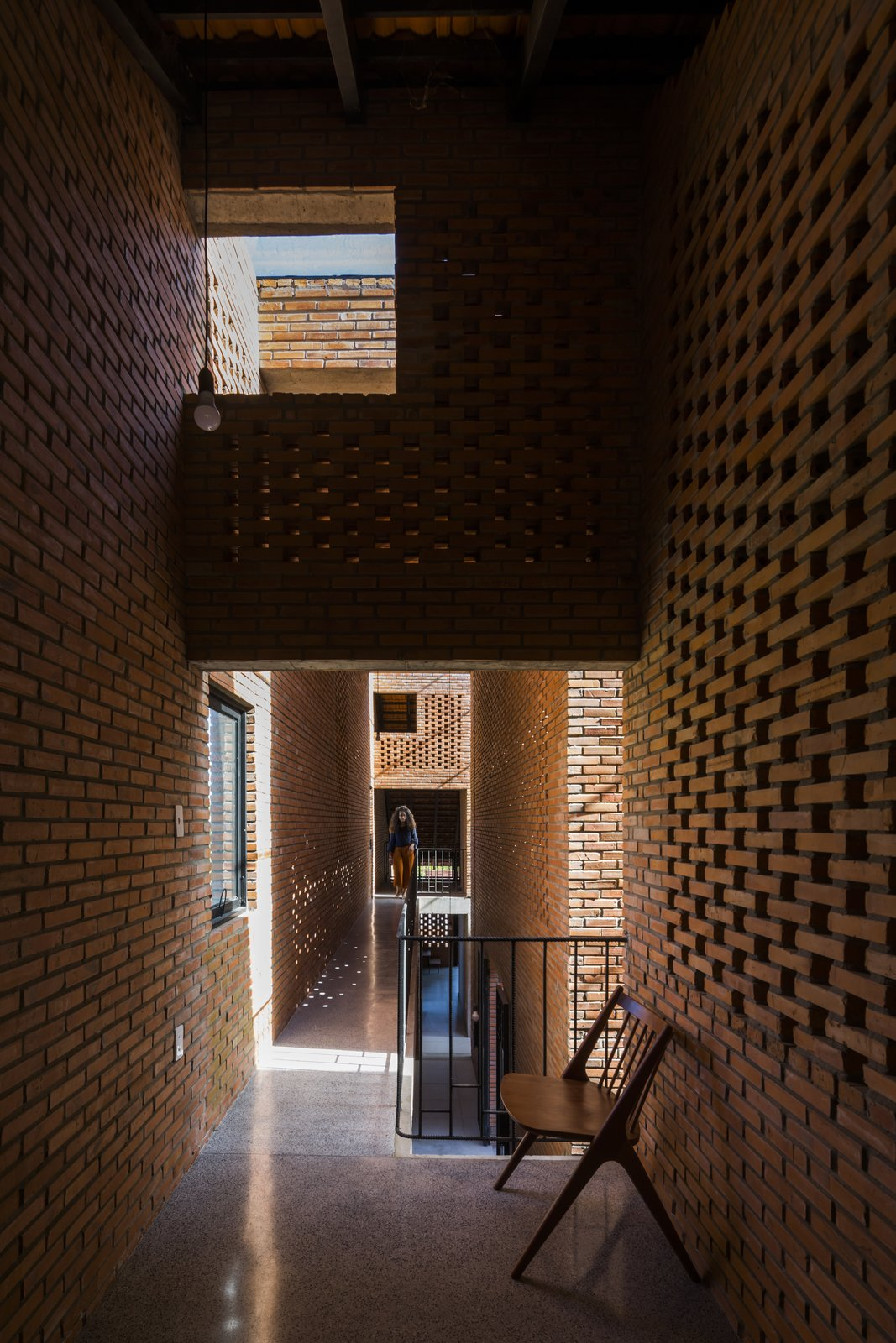 "Hallway and Concrete Floor The house employs ""open architecture"" and passive cooling techniques.  Photo 13 of 15 in Light and Shadow Help Shape This Modern Brick House in Vietnam"
