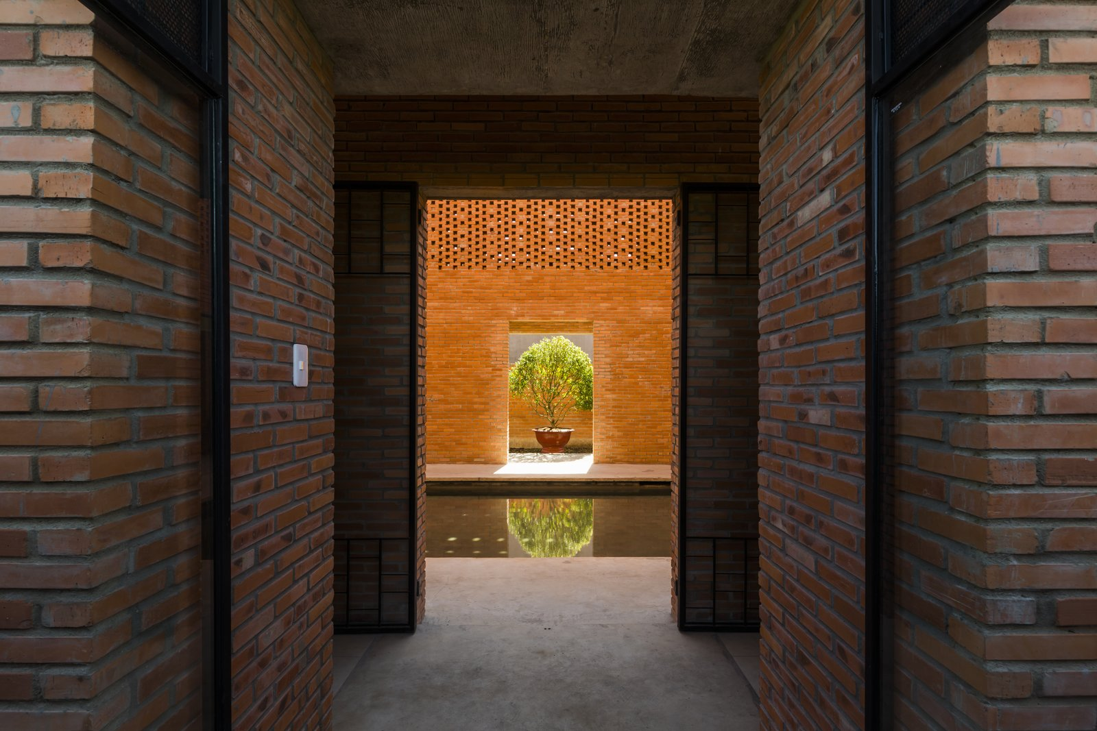Hallway and Concrete Floor Water features, which convey the balance that the philosophy of Ying and Yang calls for, is expressed in a pond-like pool in the middle of the house.  Photo 14 of 15 in Light and Shadow Help Shape This Modern Brick House in Vietnam