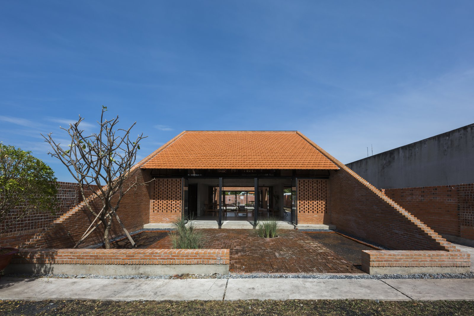 Outdoor, Front Yard, Shrubs, Trees, Large Patio, Porch, Deck, and Stone Fences, Wall Clay brick flooring in the front yard helps drain rainwater and reduce heat.  Photo 2 of 15 in Light and Shadow Help Shape This Modern Brick House in Vietnam