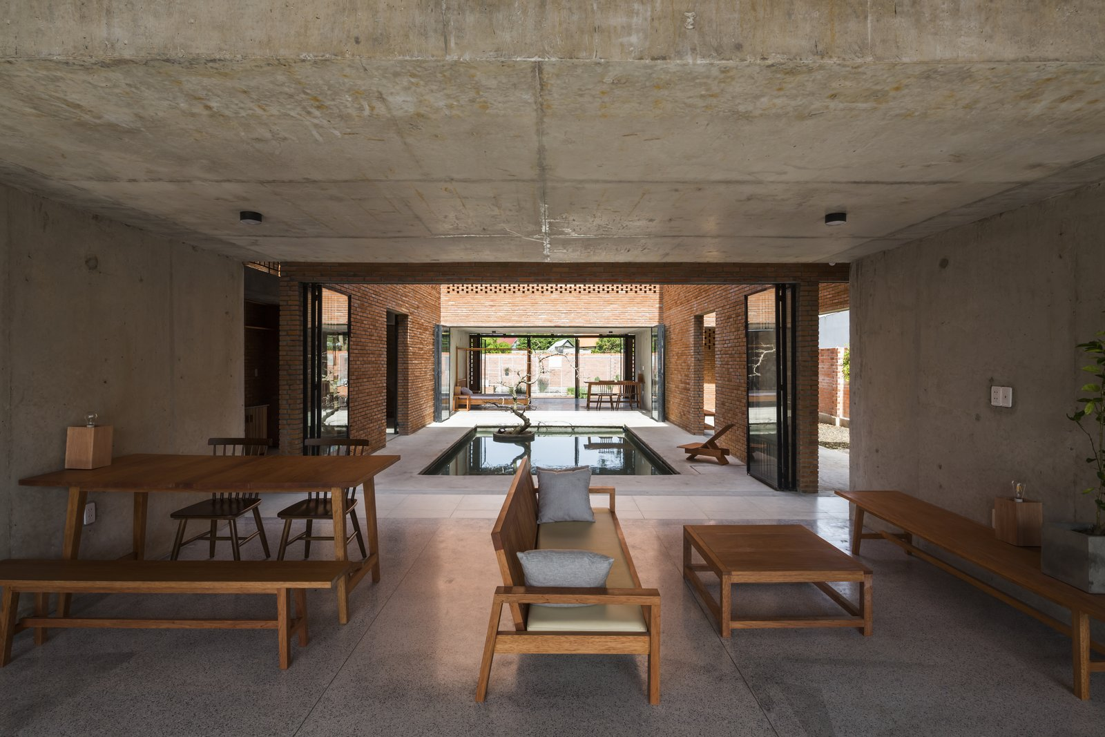 Living Room, Concrete Floor, Console Tables, Ceiling Lighting, Bench, Coffee Tables, Sofa, and Table Plenty of interior and exterior apertures bring in light and cool breezes.  Photo 3 of 15 in Light and Shadow Help Shape This Modern Brick House in Vietnam