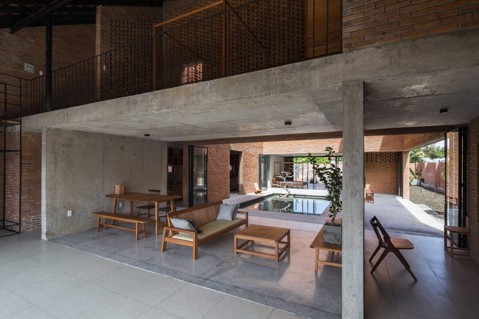 Living Room, Chair, Concrete Floor, Coffee Tables, Sofa, Ceiling Lighting, Table, and Bench The open plan living and dining room.  Photo 4 of 15 in Light and Shadow Help Shape This Modern Brick House in Vietnam