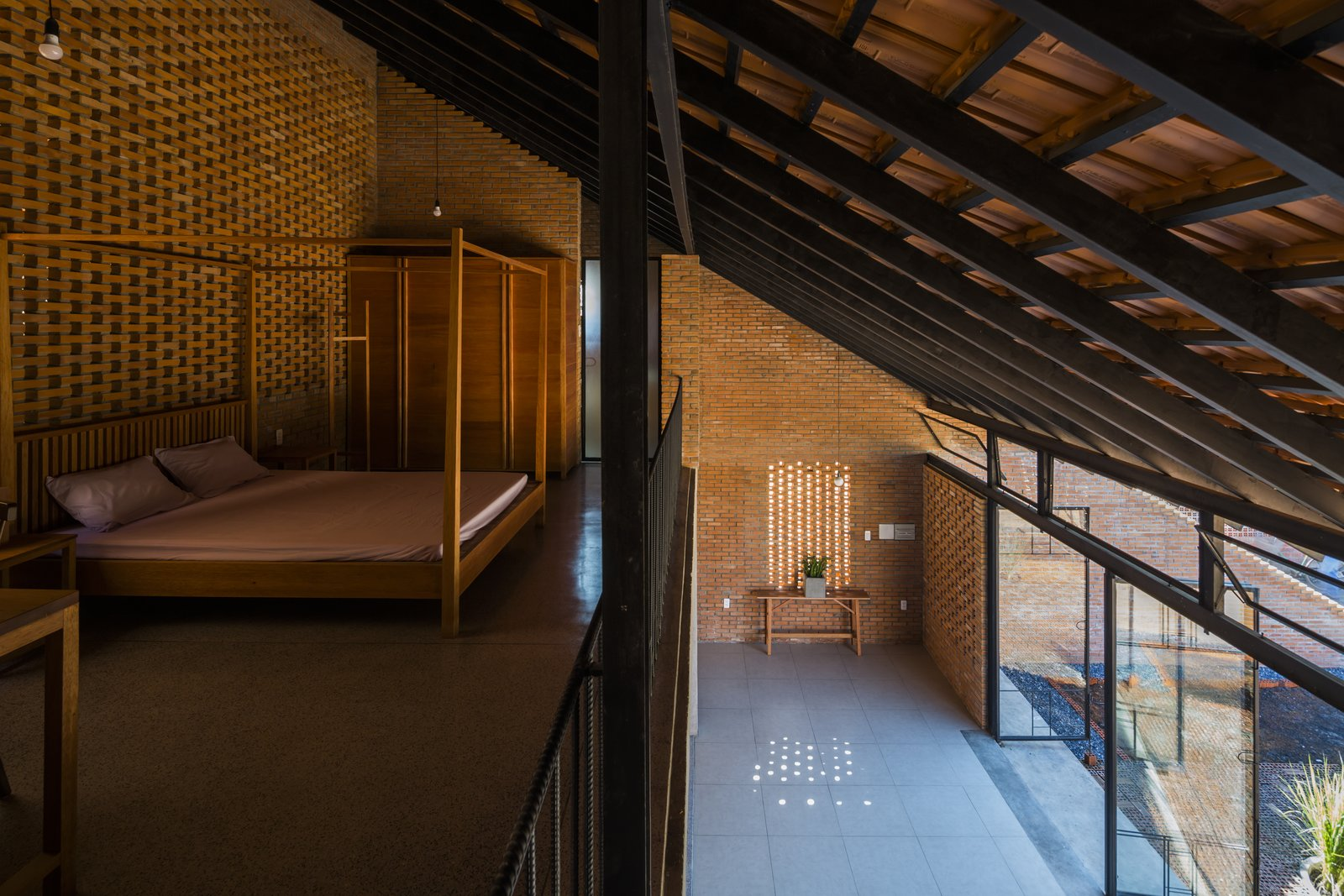 Bedroom, Bed, Concrete Floor, and Pendant Lighting The mezzanine bedroom looks down to a buffer space between the front yard and the living areas.  Photo 9 of 15 in Light and Shadow Help Shape This Modern Brick House in Vietnam