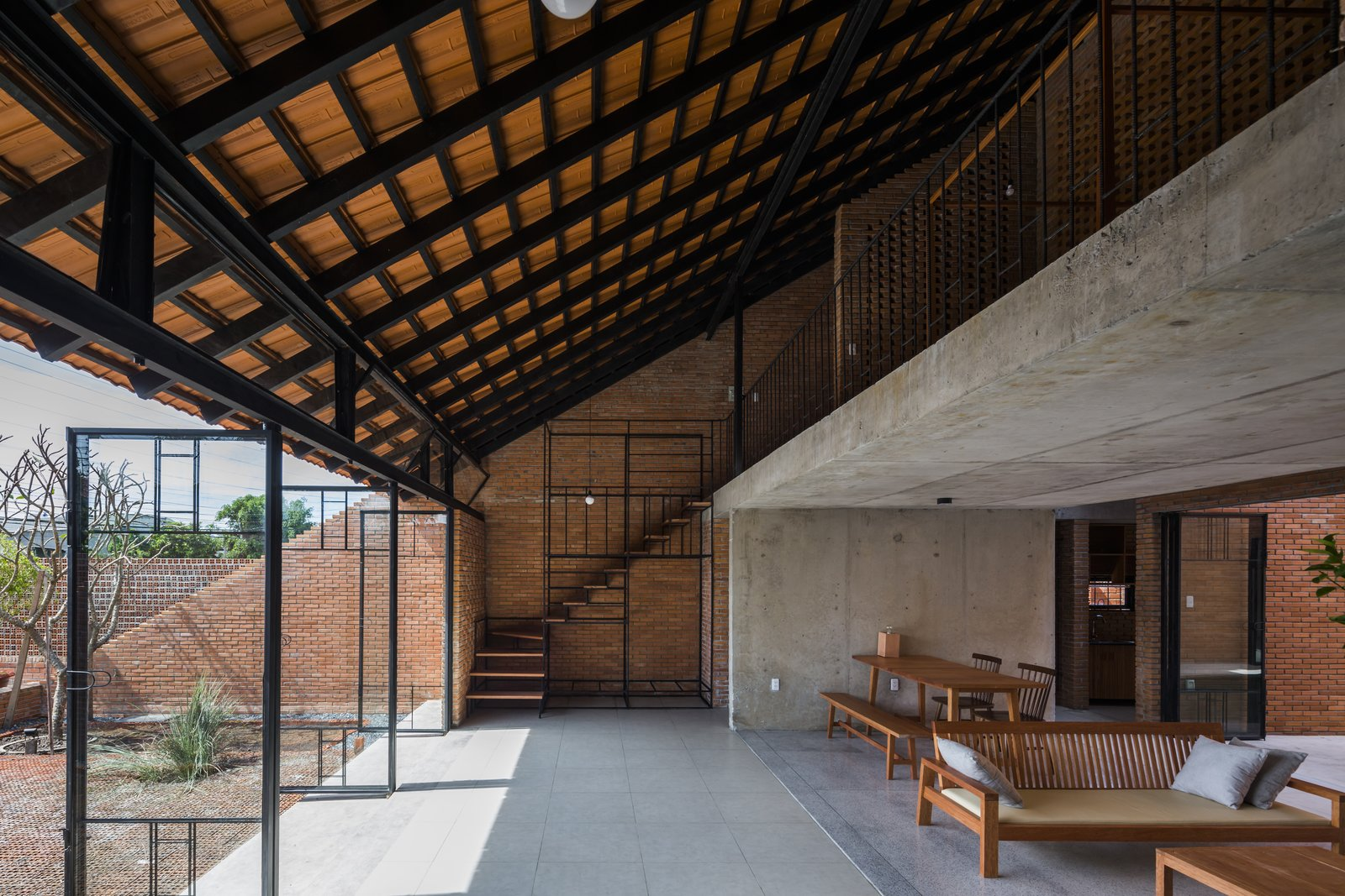 Staircase, Metal Railing, and Wood Tread Staircases are located on both ends of the residence.  Photo 12 of 15 in Light and Shadow Help Shape This Modern Brick House in Vietnam