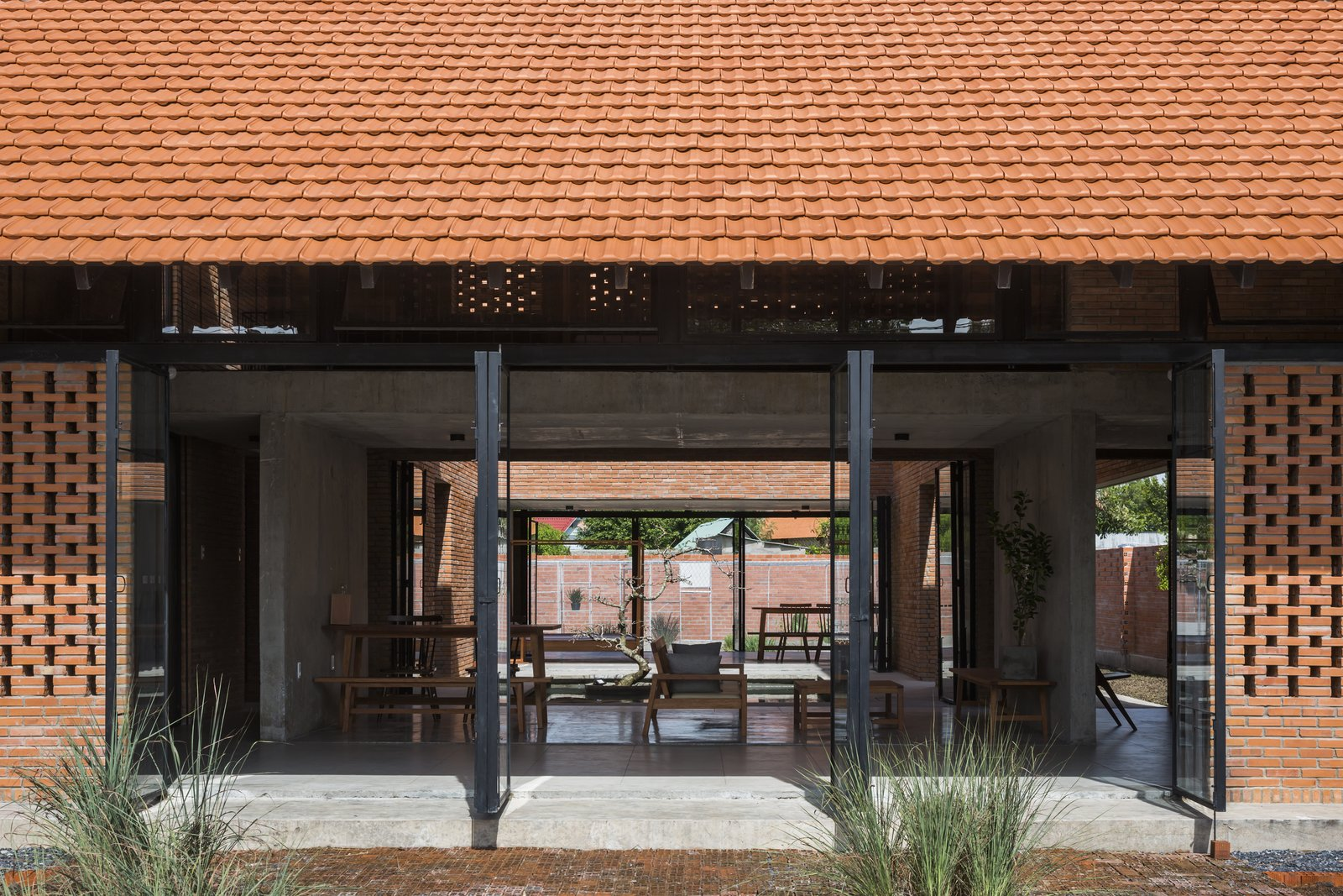 Doors, Metal, Exterior, and Swing Door Type A buffer space between the living area and the front yard.  Photo 6 of 15 in Light and Shadow Help Shape This Modern Brick House in Vietnam