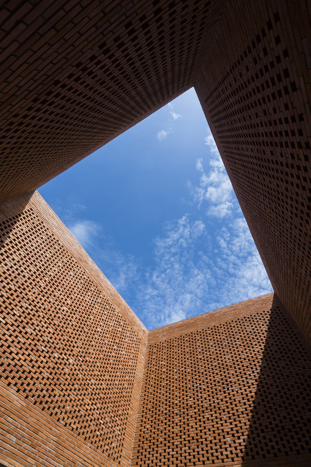 Outdoor A large expanse of blue sky seen from the courtyard.  Photo 5 of 15 in Light and Shadow Help Shape This Modern Brick House in Vietnam