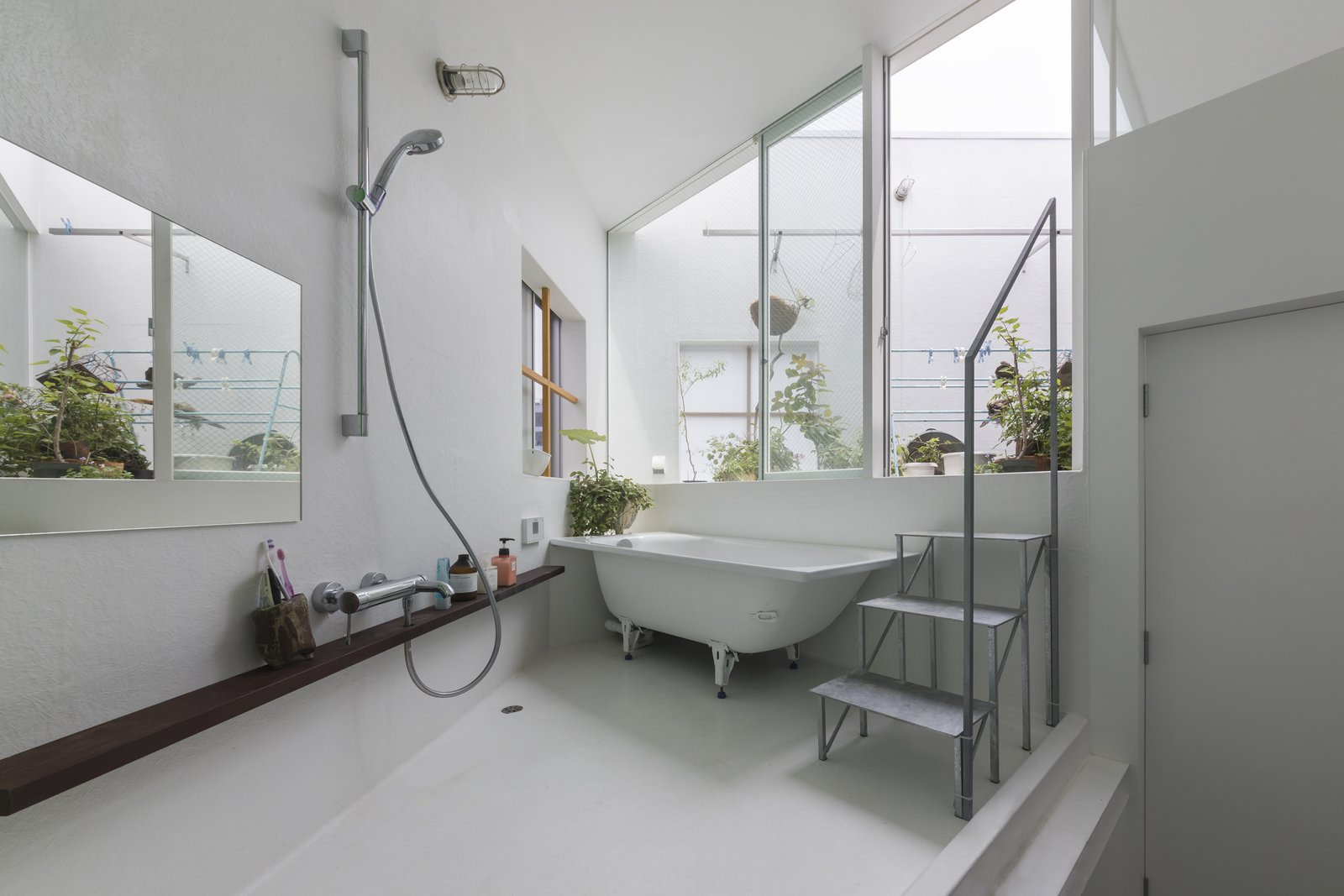 Bath Room, Open Shower, Freestanding Tub, and Wall Lighting A bathroom leads out to one of the roof terraces.  Best Photos from 13 Spiraling Platforms Increase Space and Connection in This One-Room Home