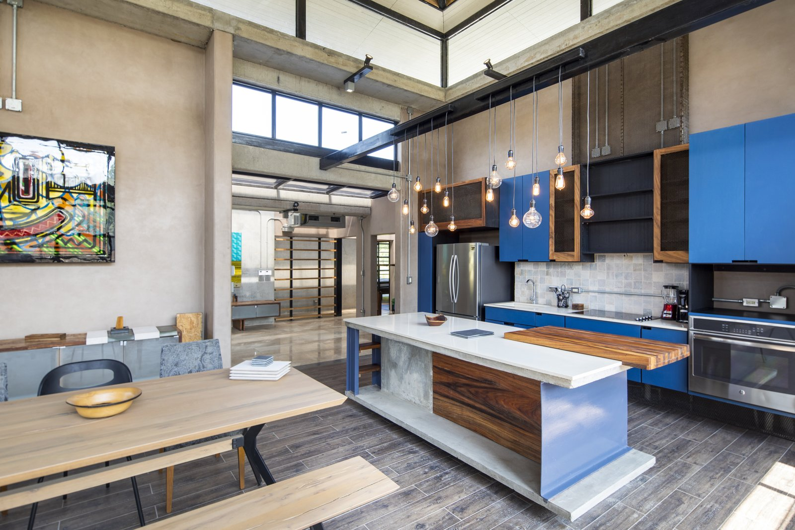 Kitchen, Pendant, Wood, Medium Hardwood, Wall Oven, Stone Tile, Concrete, Colorful, Cooktops, Refrigerator, and Undermount The kitchen and dining connects to the living room.  Kitchen Cooktops Undermount Wall Oven Stone Tile Colorful Photos from A Concrete Abode Becomes a Surfer's Paradise
