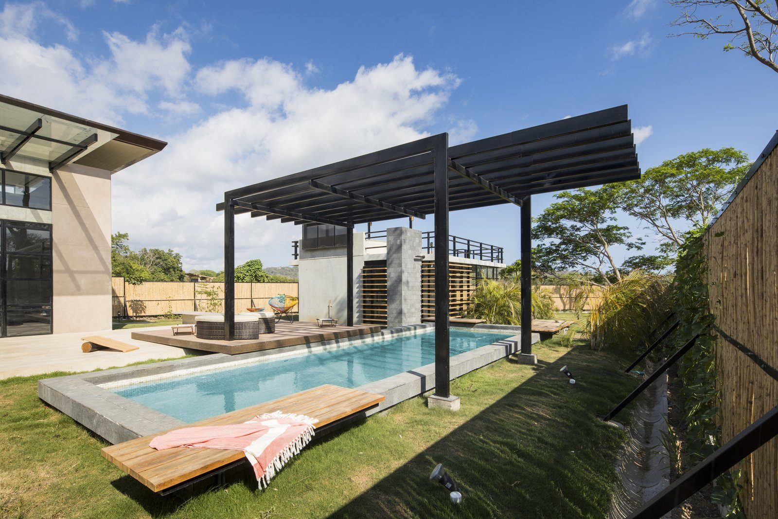 Outdoor, Grass, Wood, Back Yard, Small, Vertical, Shrubs, Lap, Small, Plunge, and Concrete A pergola keeps swimmers cool on hot days.  Outdoor Concrete Plunge Grass Photos from A Concrete Abode Becomes a Surfer's Paradise