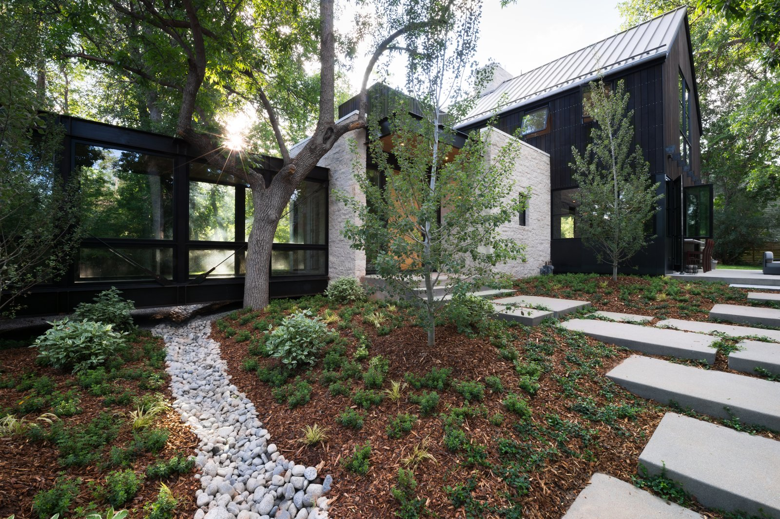 Modern farmhouse exterior yard with hardscapes and cement paver walkways.