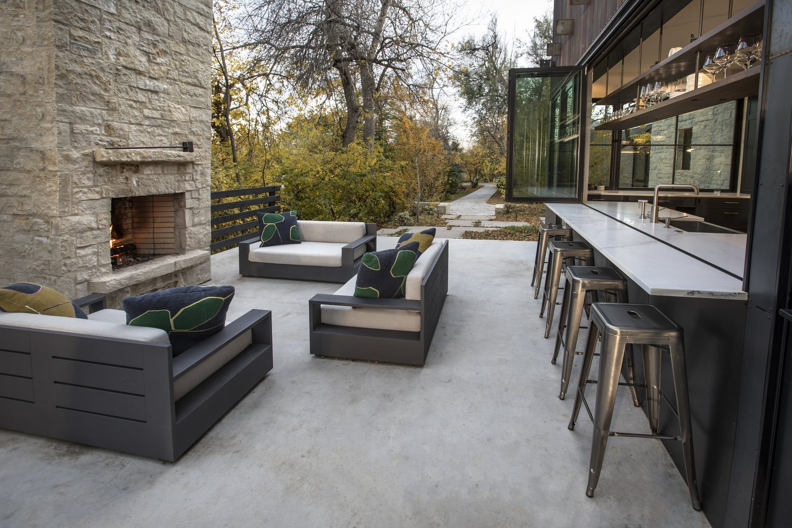 Modern farmhouse outdoor patio with bar and furniture set.