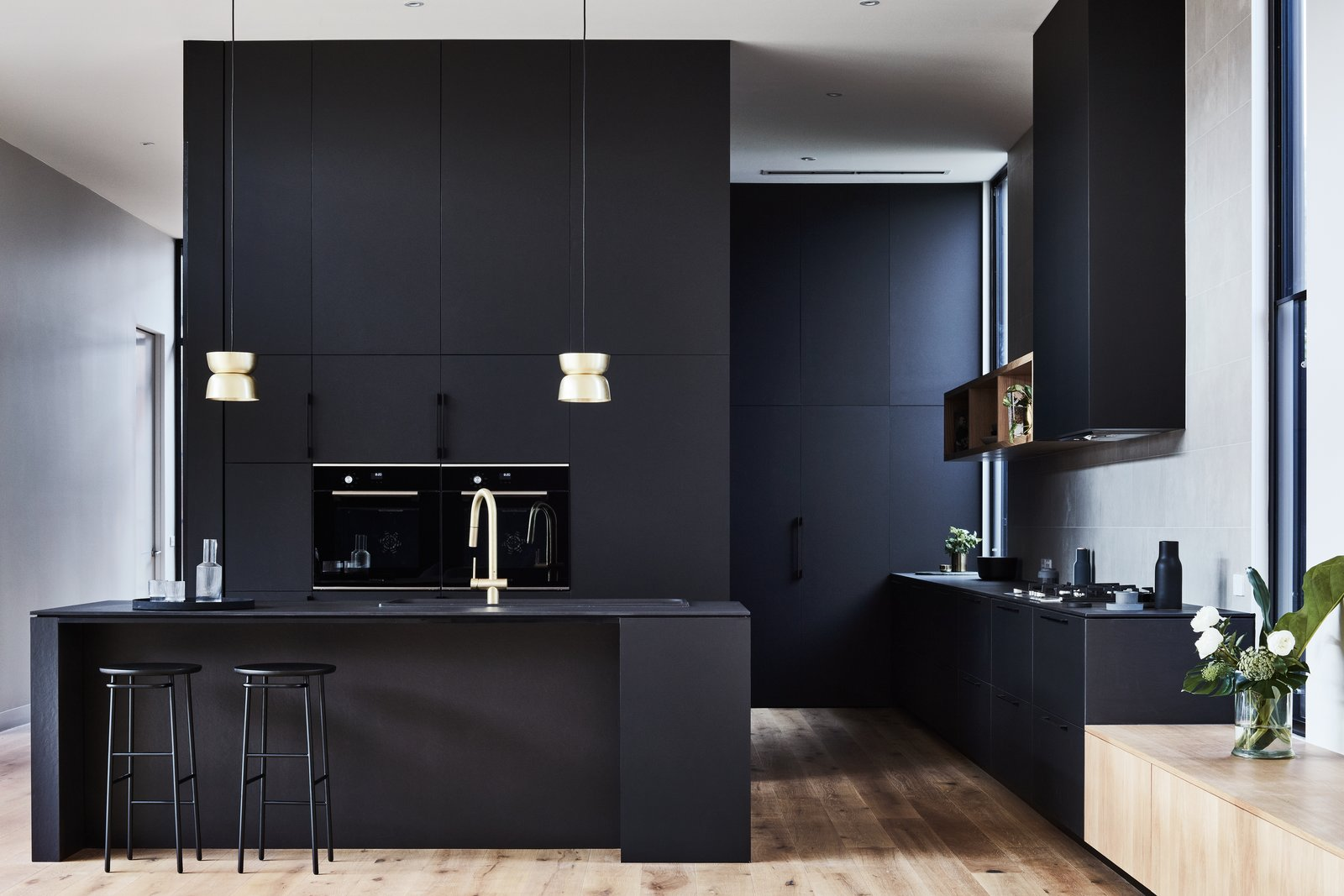 The sleek black kitchen is fitted with oak timber floors and brass accents to infuse additional sophistication into the space.