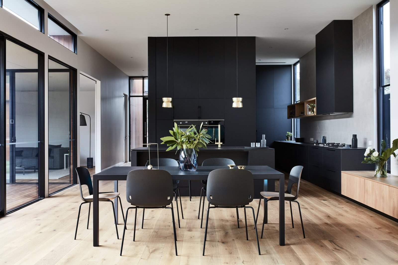Dining Room, Chair, Pendant Lighting, Medium Hardwood Floor, Table, and Recessed Lighting The simple and stylish dining set complements the dark kitchen.    Photos from A Striking Courtyard Awaits Behind These Bluestone Walls