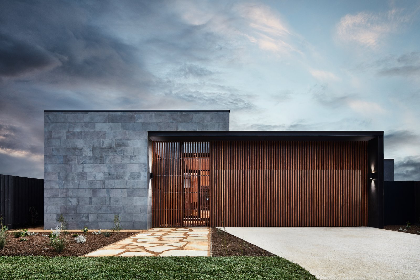 Exterior, Wood Siding Material, Flat RoofLine, House Building Type, and Stone Siding Material Horizontal slabs of bluestone and vertical hardwood slats on the exterior of the house.  Best Photos from A Striking Courtyard Awaits Behind These Bluestone Walls
