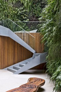 Stairs lead up from the garden to the pool and deck.