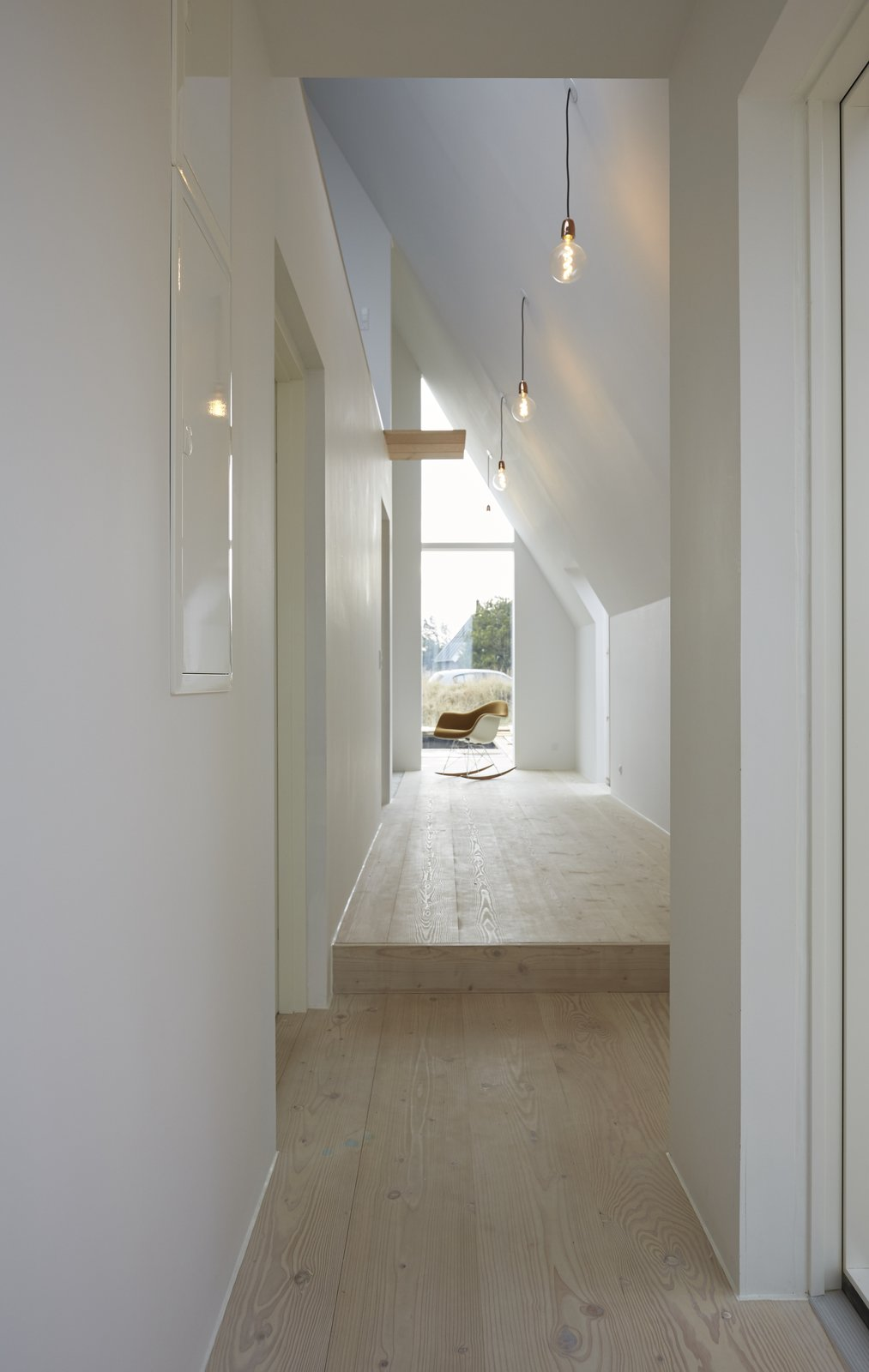 Hallway and Light Hardwood Floor Pale wooden floors and white walls brighten the interiors.  Photo 8 of 11 in Rent This Danish A-Frame For Your Next Nordic Escape