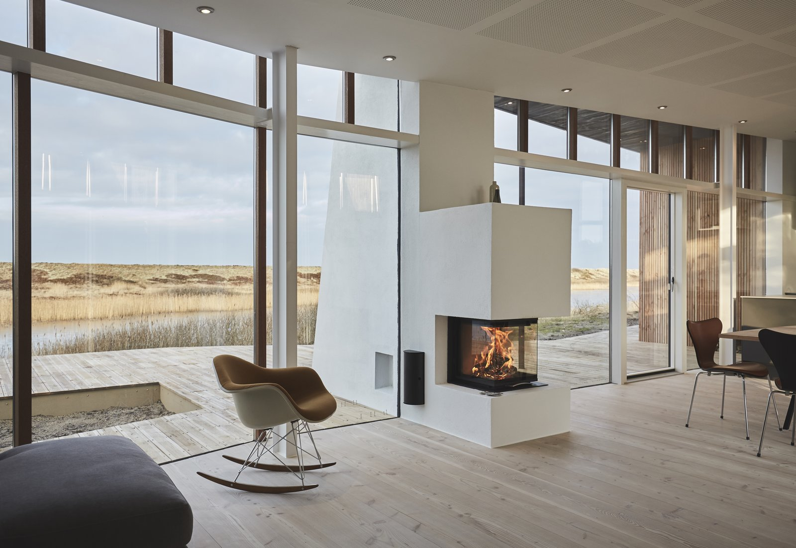Living Room, Chair, Light Hardwood Floor, Recessed Lighting, and Wood Burning Fireplace This vacation villa is integrated into nature and is surrounded by sand dunes and heathlands.  Photo 1 of 11 in Rent This Danish A-Frame For Your Next Nordic Escape
