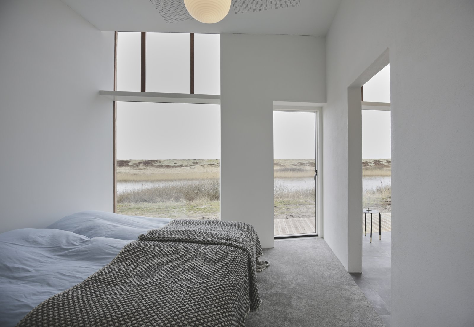 Bedroom, Carpet Floor, Bed, and Pendant Lighting The lake-facing outdoor terrace can be accessed through the bedroom.  Photo 7 of 11 in Rent This Danish A-Frame For Your Next Nordic Escape