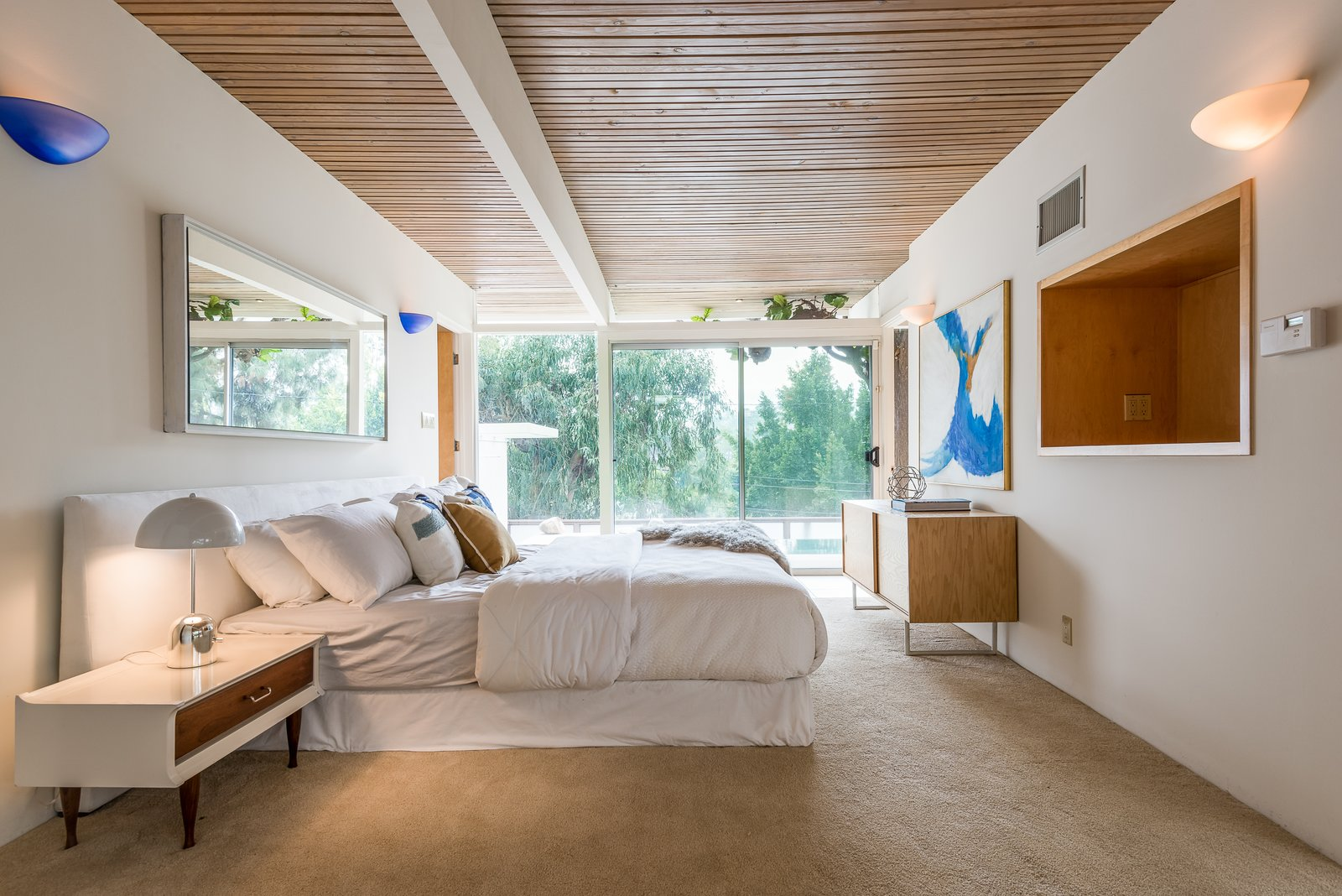 Bedroom, Night Stands, Table, Bed, Lamps, Wall, Carpet, and Storage A bedroom that looks out to canyon views.  Best Bedroom Storage Table Bed Night Stands Photos from Composer Paul Buckmaster's Midcentury Gem Asks $1.39M