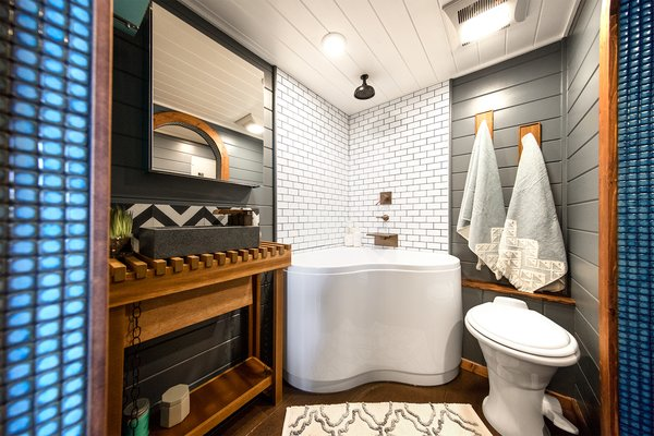 On the opposite end of the dining area is a spa-like bathroom with sliding arched doors, Moroccan tile trimming, a walk-in closet, toilet, rain shower, and a corner bathtub.