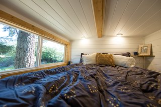 Above the bathroom is a cozy sleeping loft with a double bed. This space, along with the lofted lounge above the dining area can be accessed with a moveable ladder.