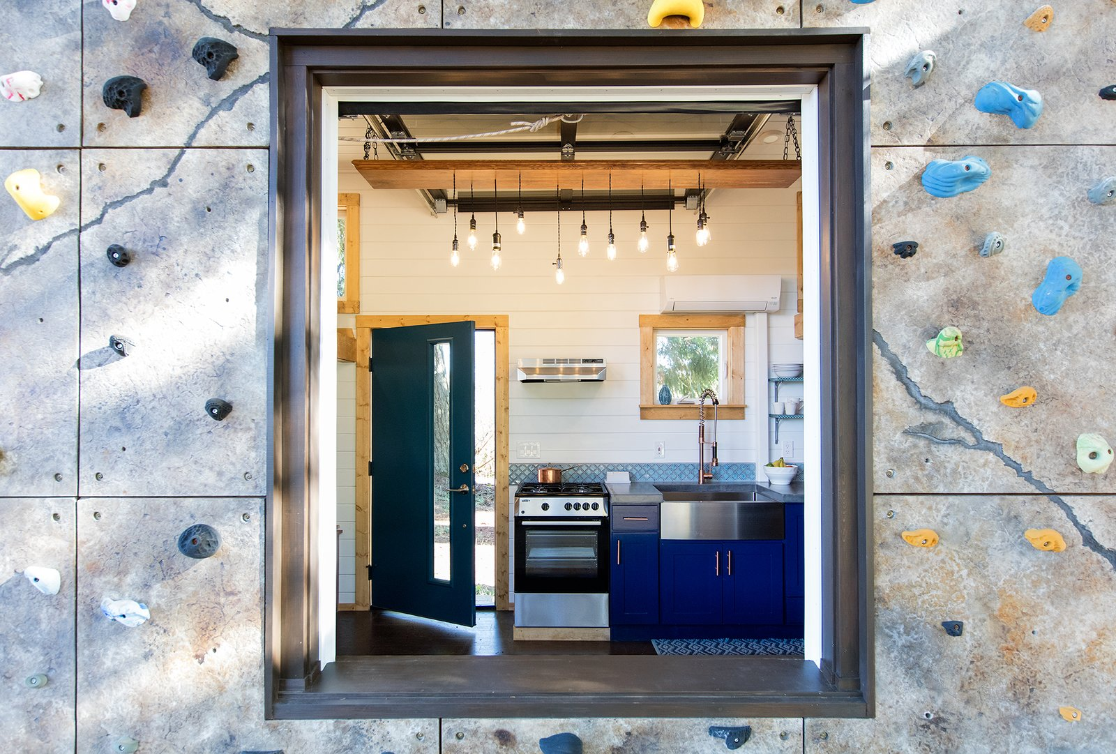 Kitchen, Range, Wall Oven, Concrete, Colorful, Undermount, Dark Hardwood, Pendant, and Range Hood A peek at the large picture window that looks into the kitchen.    Best Kitchen Range Hood Colorful Photos from This Tiny Trailer Home Lets Its Owners Climb Up the Wall