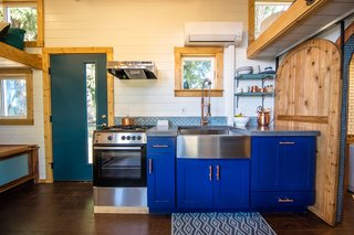 Between the dining area and bathroom is a kitchen that has concrete countertops, a stainless-steel farm sink, an oven and stove, and bright blue cabinets with elegant brass handles. These contemporary touches complement the craftsmanship and industrial-style details, giving this small dwelling a unique, modern feel.